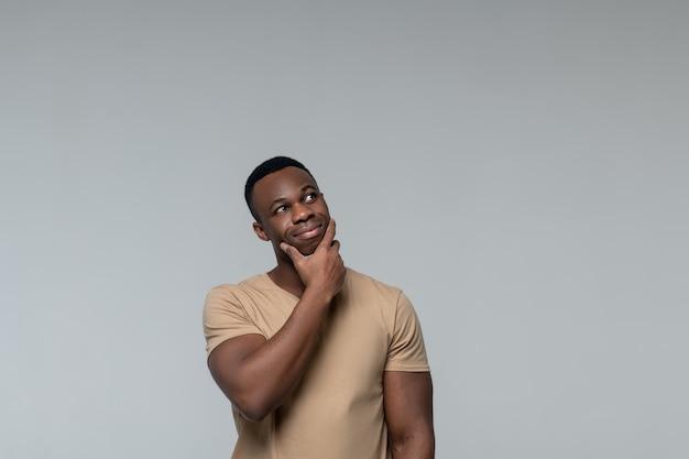 Réflexion. jeune homme afro-américain souriant pensif debout touchant le menton avec la main à la recherche de côté sur fond clair