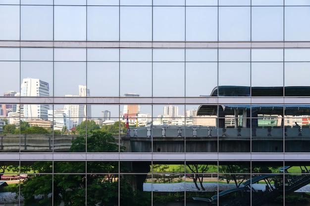 Réflexion de nombreux miroirs sur le bâtiment, voir la station de skytrain