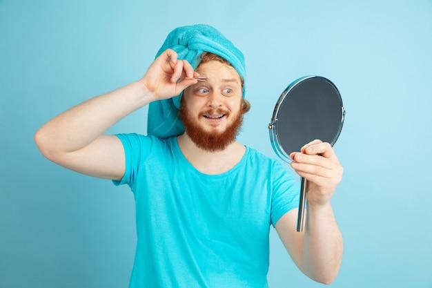 Réflexion. portrait de jeune homme caucasien dans sa journée de beauté et routine de soins de la peau. modèle masculin aux cheveux rouges constituant son sourcil à l'aide d'un miroir. soins du corps et du visage, concept de beauté naturelle et masculine.
