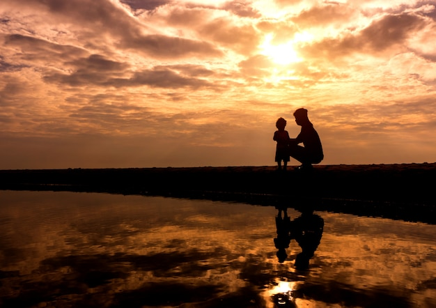 Réflexion silhouettemother avec son enfant en bas âge contre le coucher de soleil