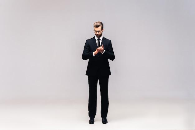 Réflexion sur la solution. prise de vue en studio sur toute la longueur d'un beau jeune homme en costume complet gardant les mains jointes et regardant la caméra