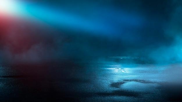 Réflexions d'asphalte humide rue sombre des rayons dans l'eau résumé smog fumée bleu foncé vide scène sombre néon projecteurs
