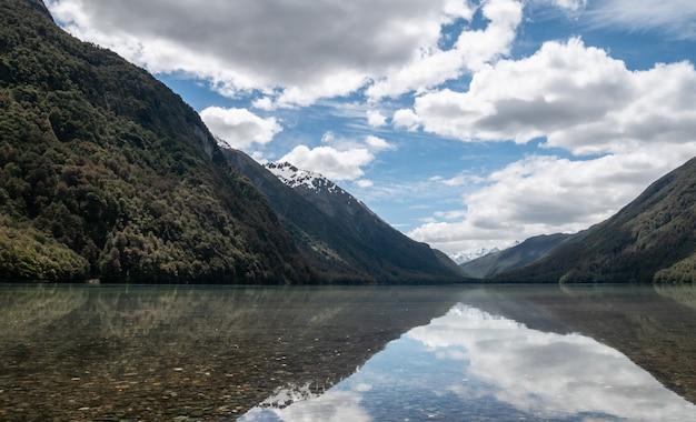 Réflexions sur un lac pendant une journée ensoleillée photo prise au parc national du lac gunn fiordland en nouvelle-zélande