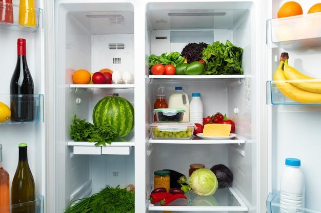 Réfrigérateur ouvert plein de fruits, légumes et boissons