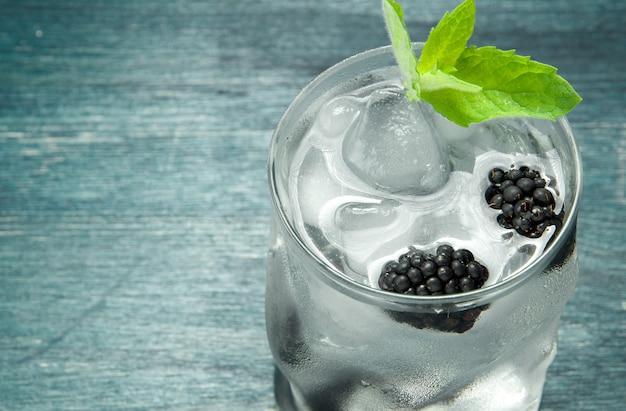 Refroidissez l'eau fraîche dans un verre avec des baies de mûre, des glaçons et de la menthe sur une table en bois.