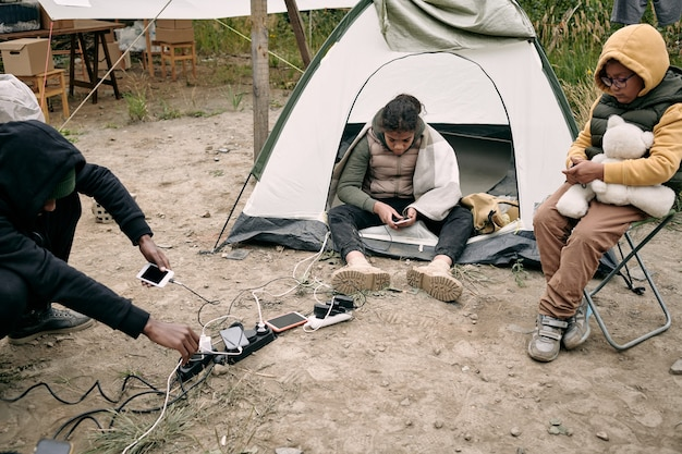 Réfugiés noirs assis par terre et utilisant des gadgets qui se rechargent dans des prises de courant à l'extérieur