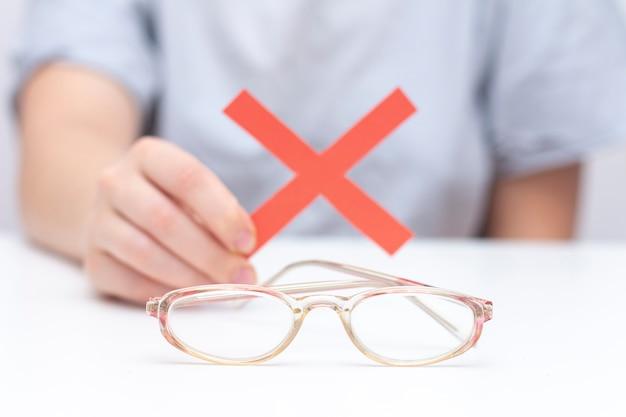 Refus de lunettes pour la vue. les mains refusent les lunettes. croix sur des verres. amélioration de la vision, correction de la vision au laser.
