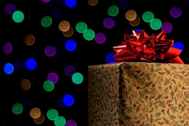 Regalo de navidad con luces de colores al fondo