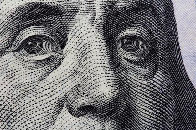 Le regard de benjamin franklin sur un billet de cent dollars.