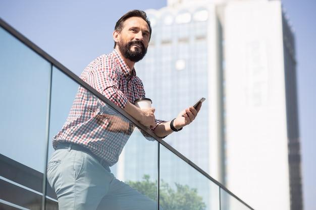 Regard confiant. homme barbu joyeux à l'aide de son téléphone tout en profitant de la vue urbaine