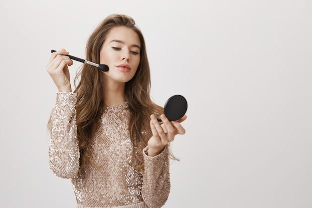 Regard de femme féminine dans le miroir appliquer le maquillage