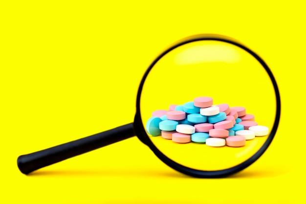 Un regard à travers une loupe sur un tas de pilules multicolores sur jaune