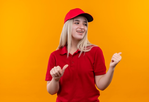 Regardant à l'arrière souriant livraison jeune femme portant un t-shirt rouge et une casquette en orthèse dentaire points à l'arrière sur un mur orange isolé