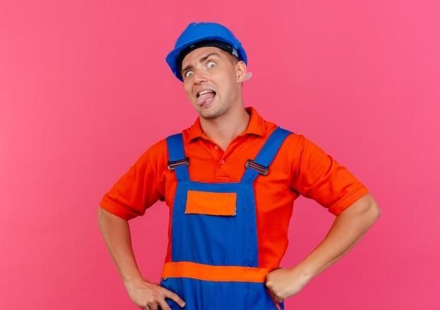 Regardant la caméra jeune constructeur masculin portant l'uniforme et un casque de sécurité montrant la langue et mettant les mains sur la hanche isolé sur fond rose