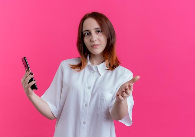 Regardant la caméra jeune fille rousse tenant le téléphone et tenant la main à la caméra isolée sur fond rose