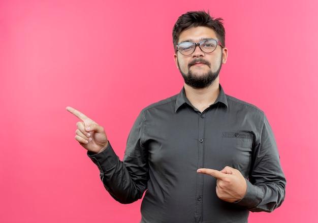 Regardant la caméra jeune homme d'affaires portant des lunettes points sur le côté