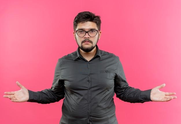 Regardant la caméra jeune homme d'affaires portant des lunettes tenant les mains sur les côtés