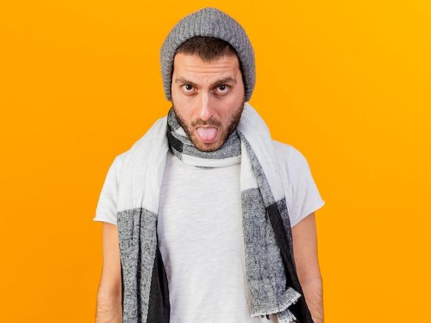 Regardant la caméra jeune homme malade portant un chapeau d'hiver et une écharpe montrant la langue isolée sur fond jaune