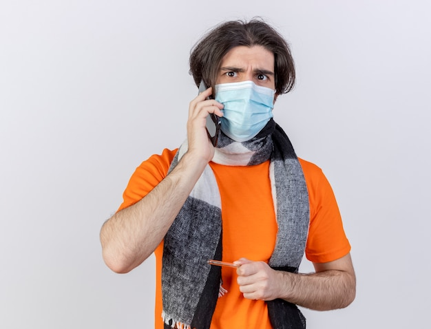 Regardant la caméra jeune homme malade portant un foulard et un masque médical parle au téléphone tenant un thermomètre isolé sur fond blanc