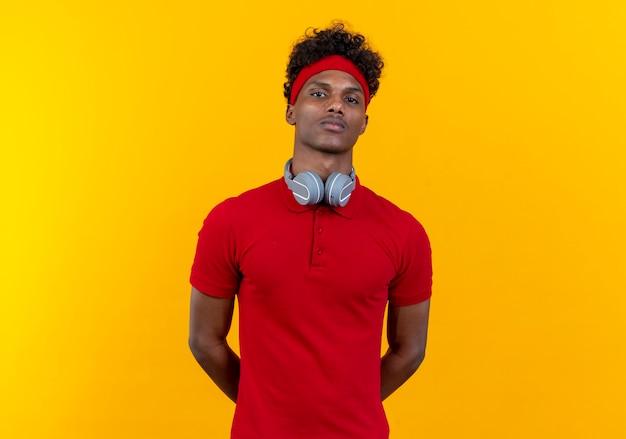 Regardant la caméra jeune homme sportif afro-américain portant un bandeau et un bracelet avec des écouteurs en gardant les mains derrière le dos isolé sur fond jaune