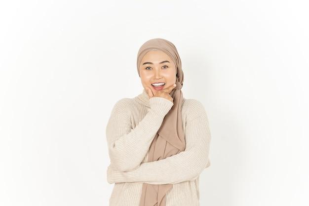 En regardant la caméra et le sourire de la belle femme asiatique portant le hijab isolé sur fond blanc