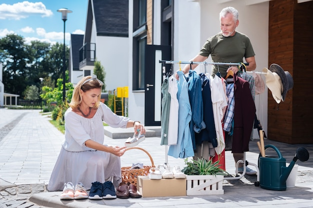 En regardant des chaussures. jolie femme aux cheveux blonds portant une robe rayée à la recherche de chaussures à la vente-débarras en la visitant avec son mari