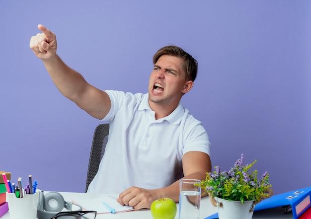 Regardant à côté en colère jeune étudiant beau mâle assis au bureau avec des outils scolaires points sur le côté
