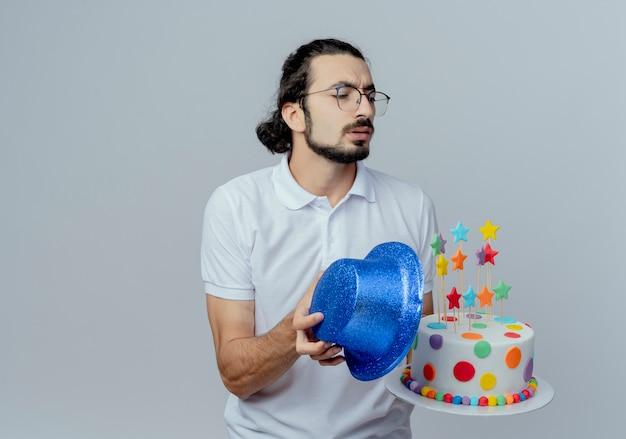 Regardant à côté confus bel homme tenant un gâteau avec un chapeau bleu isolé sur fond blanc
