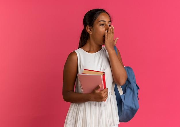 Regardant à côté effrayé jeune écolière portant sac à dos holding notebook avec livre et bouche couverte avec la main