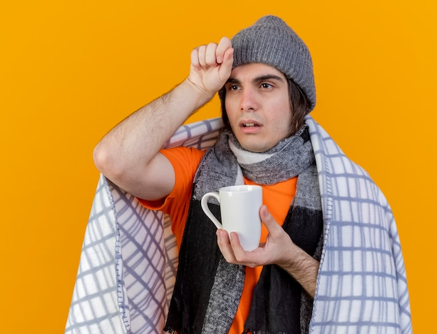 Regardant à côté faible jeune homme malade portant un chapeau d'hiver avec écharpe enveloppé dans un plaid tenant une tasse de thé mettant la main sur le front isolé sur fond orange