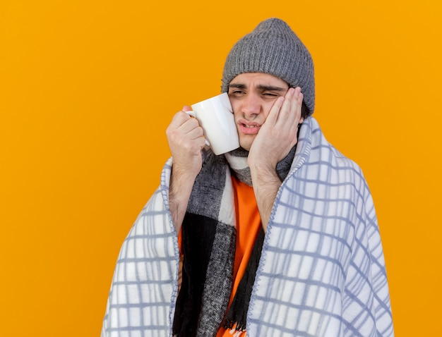 Regardant à côté faible jeune homme malade portant un chapeau d'hiver avec écharpe enveloppée de plaid mettant la main