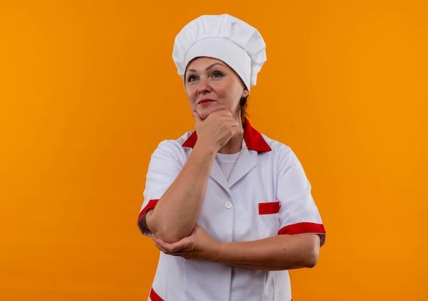 Regardant à côté femme d'âge moyen cuisinier en uniforme de chef mettant la main sur le menton sur mur jaune isolé