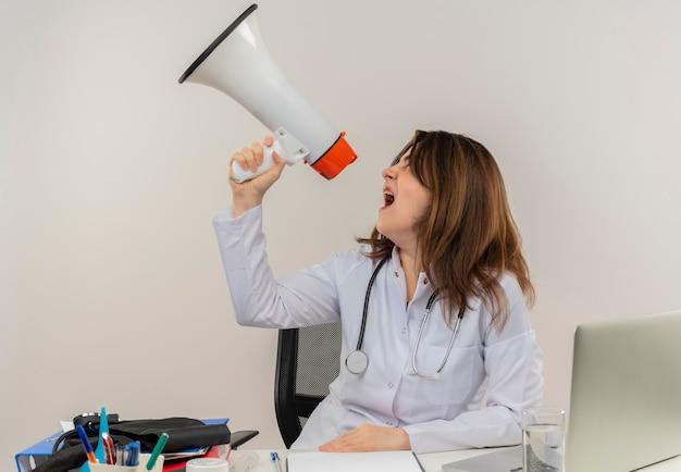 Regardant à côté femme médecin d'âge moyen portant portant une robe médicale avec stéthoscope assis au bureau de travail sur un ordinateur portable avec des outils médicaux parle sur haut-parleur sur mur blanc avec espace de copie