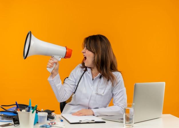 Regardant à côté femme médecin d'âge moyen portant une robe médicale avec stéthoscope assis au bureau de travail sur un ordinateur portable avec des outils médicaux parle sur haut-parleur sur mur orange isolé avec espace de copie