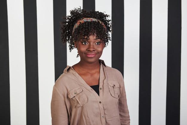 En regardant de côté. fille afro-américaine souriante se tient dans le studio avec des lignes verticales blanches et noires à l'arrière-plan
