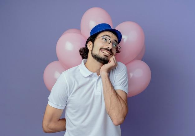 Regardant à côté heureux bel homme portant des lunettes et un chapeau bleu debout devant des ballons et mettant la main sur le menton isolé sur fond violet