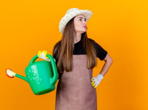 Regardant à côté heureux belle fille de jardinier portant uniforme et chapeau de jardinage avec des gants tenant un arrosoir et mettant la main sur la hanche isolé sur fond orange