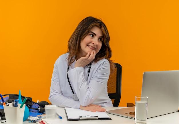 Regardant à côté heureux femme médecin d'âge moyen portant une robe médicale avec stéthoscope assis au bureau de travail sur un ordinateur portable avec des outils médicaux mettant la main sur le menton sur un mur orange avec espace de copie