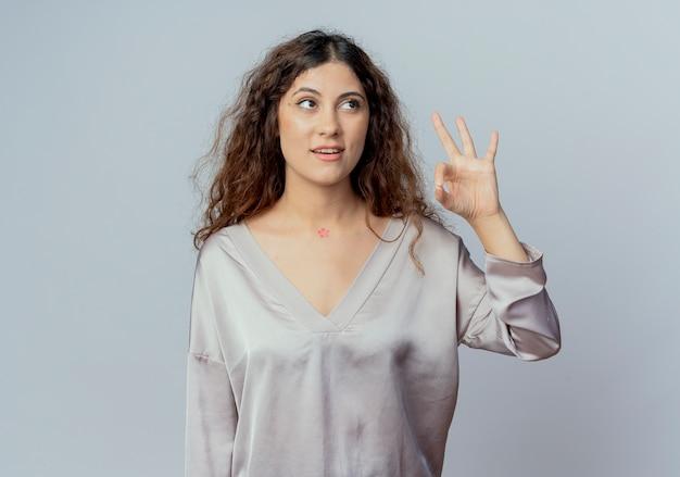 Regardant à côté heureux jeune employé de bureau jolie femme montrant le geste okey isolé sur mur blanc
