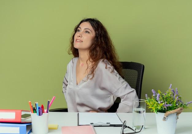 En regardant côté heureux jeune jolie employée de bureau assis au bureau
