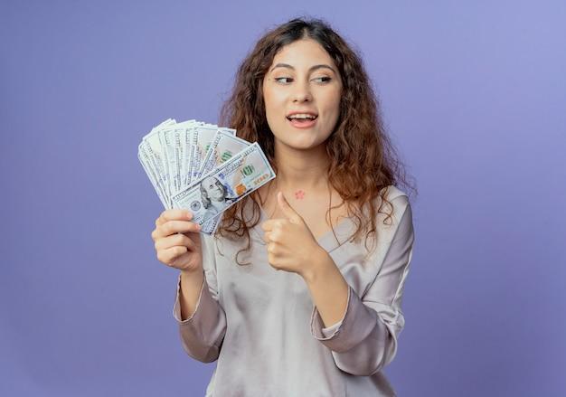 Regardant à côté heureux jeune jolie fille tenant de l'argent et son pouce vers le haut isolé sur mur bleu
