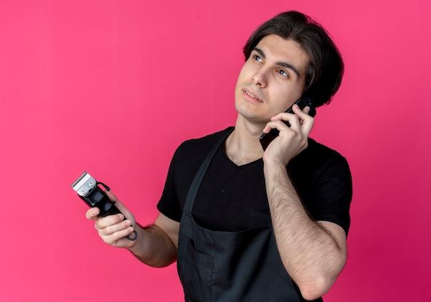 Regardant à côté jeune beau coiffeur masculin en uniforme tenant une tondeuse à cheveux et parle au téléphone