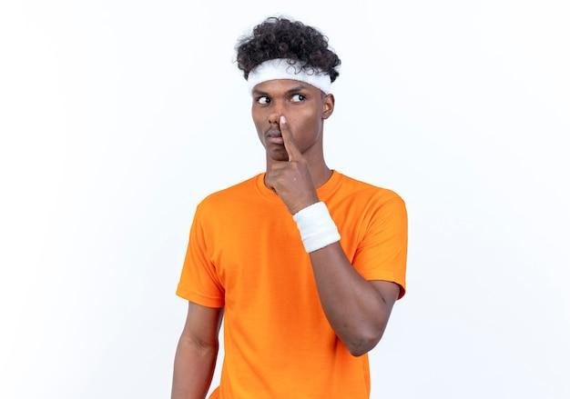 Regardant le côté jeune homme sportif afro-américain portant bandeau et bracelet mettant le doigt sur le nez isolé sur fond blanc