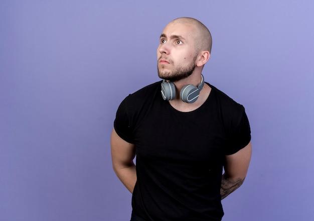Regardant à côté jeune homme sportif strict portant des écouteurs sur le cou tenant les mains derrière le dos isolé sur fond violet