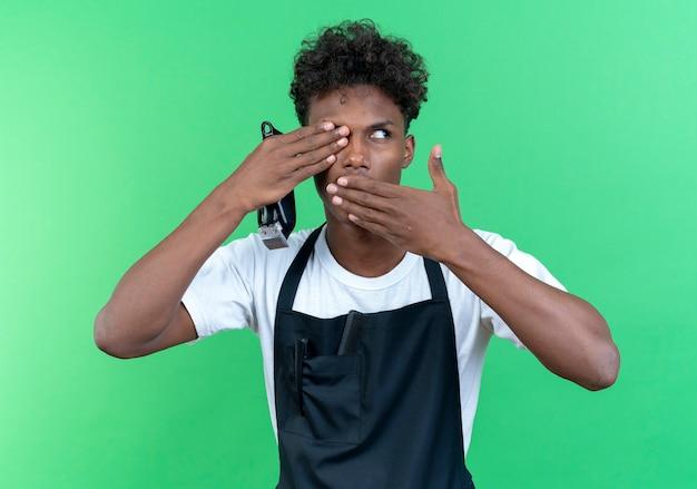 Regardant à côté les jeunes hommes afro-américains coiffeur portant des uniformes tenant des tondeuses à cheveux couvertes la bouche et les yeux avec les mains isolés sur le mur vert