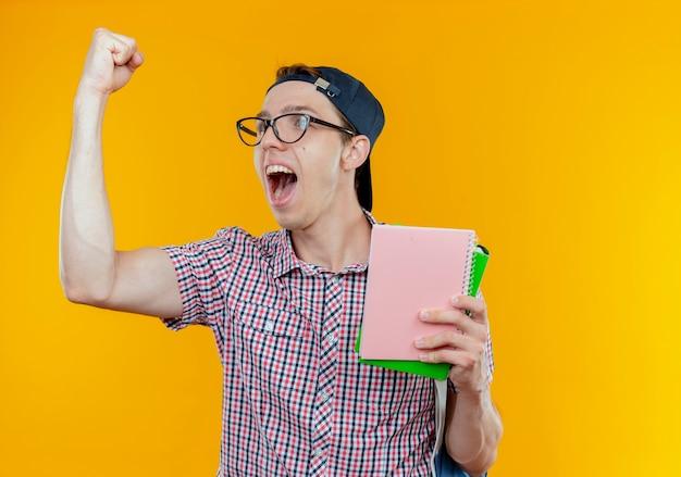 Regardant le côté joyeux jeune étudiant garçon tenant le cahier et montrant le geste oui