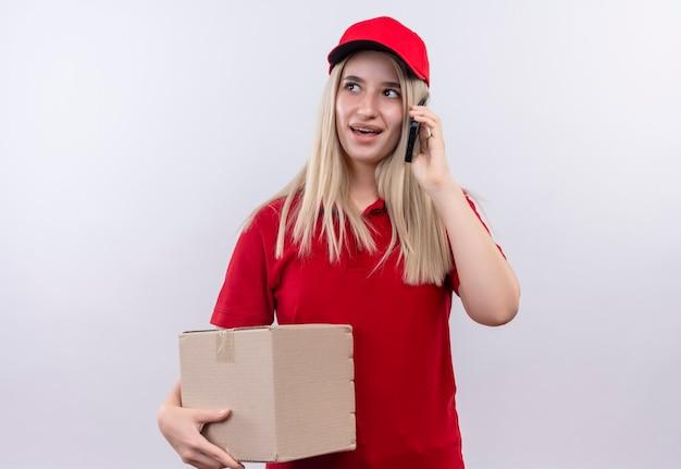 Regardant à côté livraison jeune femme portant un t-shirt rouge et une casquette en orthèse dentaire tenant la boîte et pseakes sur téléphone sur mur blanc isolé