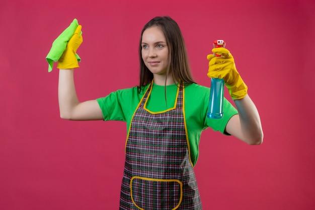 Regardant le côté nettoyage jeune femme portant l'uniforme dans des gants soulevant un spray de nettoyage et un chiffon sur sa main sur un mur rose isolé