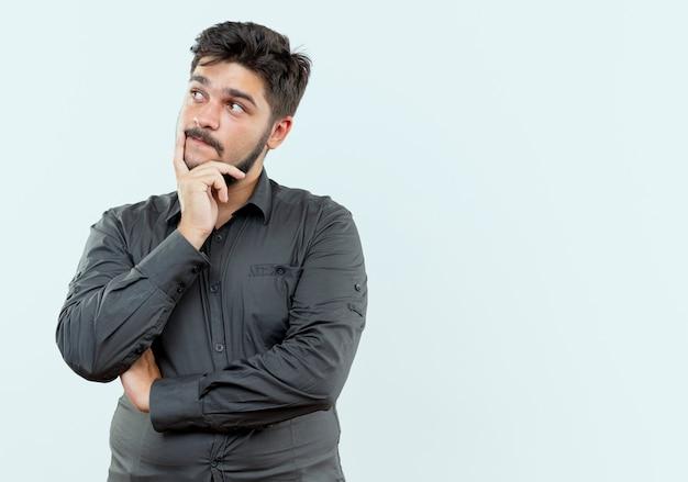 Regardant le côté pensant jeune homme d'affaires mettant la main sur le menton isolé sur fond blanc avec copie