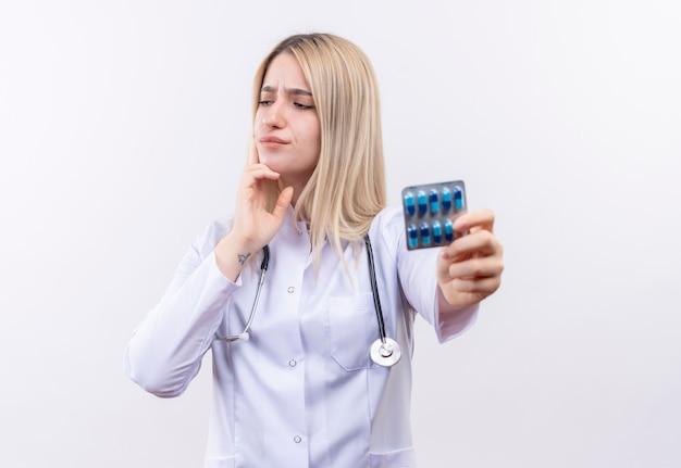 Regardant à côté de la pensée médecin jeune fille blonde portant un stéthoscope et une robe médicale tenant des pilules mis sa main sur le menton sur un mur blanc isolé